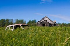 Old Car old house. Photo of an abandoned car and home peeking out of the grass Royalty Free Stock Photography
