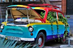 An old car painted in rainbow colors, covered by plants. royalty free stock image