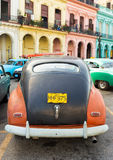 Old car parked near colorful buildings in Havana Stock Photo