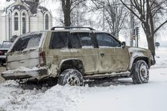 An old car parked on a snow-covered road. An old car, a jeep, parked on a snow-covered road Stock Photo