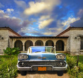 Old car parked in tropical house, cuba. Front view in vintage american car parked in tropical residence, cuba Royalty Free Stock Images