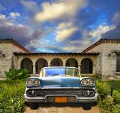 Old car parked in tropical house, cuba. Front view in vintage american car parked in tropical residence, cuba Stock Photos