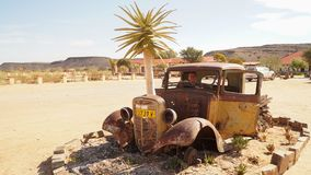 Old Car ruins at the Canyon Roadhouse in Namibia. Trees growing in the car wreck stock photo