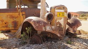 Old Car ruins at the Canyon Roadhouse in Namibia. Trees growing in the car wreck royalty free stock photography