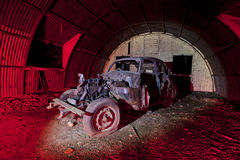 Old car rusting in an old ww2 shelter stock image