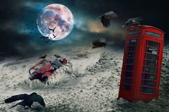 Old car in the sand , red telephone booth, crows, cloudy sky. Photo manipulation. Sinister scene by night, with dark scary horror atmosphere. Photo manipulation stock photos