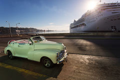 Old car on street of Havana with cruise ship in background at su. Nrise, Cuba Stock Photography