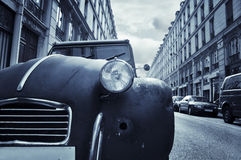 Old car in the street of Paris. A very old car (Citroen 2CV) parked on the side of a street in Paris, France stock image