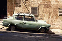 Old car in a street of Valletta, Malta. A very old car is parked in a narrow street of Valletta, the capital city of Malta Stock Photography