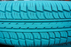 Old car tire painted with turquoise color Stock Photos