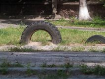 Old car tires dug into the ground. Like a fence in the playground stock photography