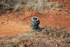 Old car tyres on single pile left on corner of local motocross racing track used for protection in case of fall surrounded with. Dry grass and wet soil on warm royalty free stock images