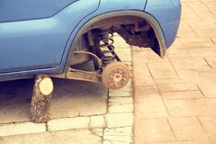 An old car waiting for the steering wheel. A car without a tyre and supported by a jack that is a wooden stump. Garage photo check transport change workshop stock photos