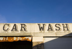 Old car wash sign. On derelict building with blue sky background Royalty Free Stock Images