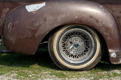 Old car wheel. The side of a scratched and marked old brown car with a whitewall tire Stock Images