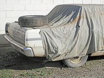 Old Car wiith New Spare Tire. An old car covered and stored for restoration Stock Image