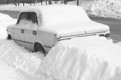Old car in winter in snow on road, black and white photo Royalty Free Stock Photos