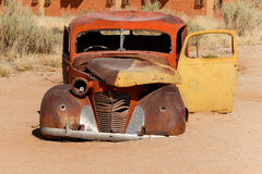 Old car wreck lying in the desert Royalty Free Stock Photo