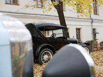 An old car in the yard which is covered with yellow maple leaves royalty free stock photo