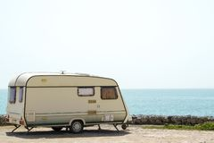 Old caravan on the shore. Old retro caravan staying on a beautiful sea coast Royalty Free Stock Photo