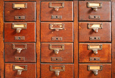Old card catalog. Old wooden card catalog with brass pulls and some old yellowed blank paper labels Royalty Free Stock Image