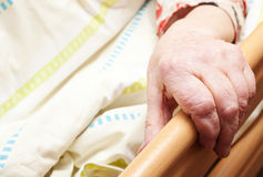 Old care-dependent person. Hand of a care-dependent person in bed Stock Image
