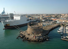 Old Cargo Ship Docked. In Civitavecchia (Italy) near a old coastal fortress and the touristic harbor Stock Images