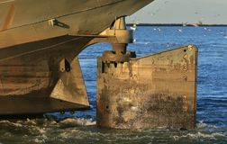Old cargo Ships rudder. Ships rudder extends above the water line as the empty ship leaves port for a new load of cargo royalty free stock photo