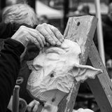 Old Carpenter carving a wooden carnival mask. Stock Image