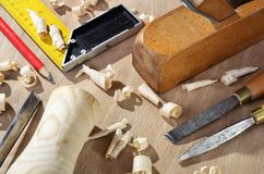 Old carpenter plane tools and wood shavings. On wooden background stock image