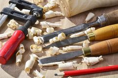 Old carpenter plane tools and wood shavings. On wooden background royalty free stock images