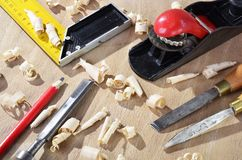 Old carpenter plane tools and wood shavings. On wooden background royalty free stock photography