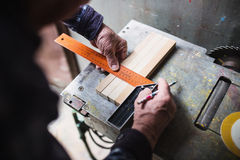 Old carpenter taking measurement Royalty Free Stock Image