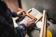 Old carpenter taking measurement Stock Image