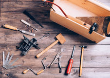 Old carpenter tools. On brown wooden background stock photography