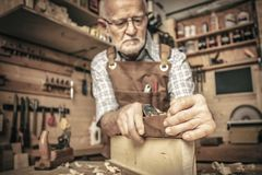 Carpenter uses a planer royalty free stock photo