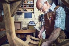 Old carpenter at work stock photo