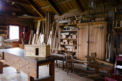 Old carpenters shop with the workpiece and tools. Interior of carpentry workshop with workbench, tools hanging on the wooden walls, wooden blank and finished Royalty Free Stock Photos