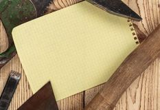 Old carpentry tools and a piece of notebook. On a wooden background stock images