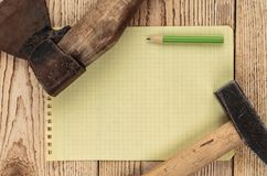 Old carpentry tools and a piece of notebook. On a wooden background stock photography