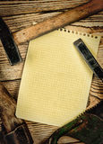 Old carpentry tools and a piece of notebook Royalty Free Stock Images