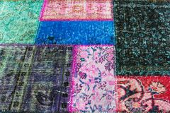 Old carpet of multi-colored rags. Beautiful background of old colored carpet scraps sewn together with a flower pattern Stock Photography