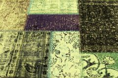 Old carpet of multi-colored rags. Beautiful background of old colored carpet scraps sewn together with a flower pattern Royalty Free Stock Photos