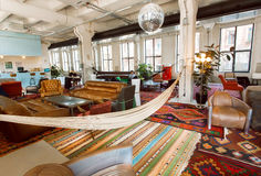 Old carpets and couches inside the loft style hotel lobby with big windows Stock Photography