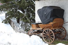 Old carriage in a snowy garden Stock Photo