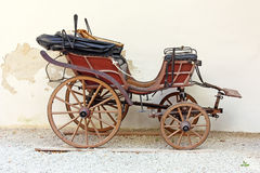 Old carriage. Old wooden carriage in front of wall Royalty Free Stock Photos