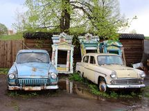Old cars on the background of carved multi-colored shutters. Russia, 2013. Photographed in the Yaroslavl region in the courtyard of a small restaurant Royalty Free Stock Photography