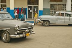Old cars in Cuban village near the El Rincon driving past old store and villagers Royalty Free Stock Photography