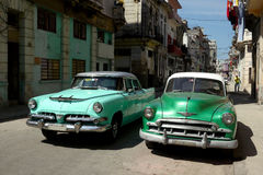 Old cars in downtown backstreet Havana Stock Photos