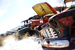 Old cars at junkyard. Old cars in the snow at a rural junkyard. shot with a lensbaby - limited depth of field with focus on front grill. legal note - license Royalty Free Stock Image
